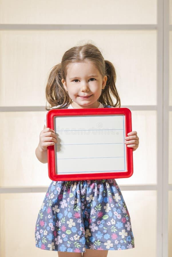 Menina expressivo que guarda uma placa magnética vazia imagem de stock royalty free