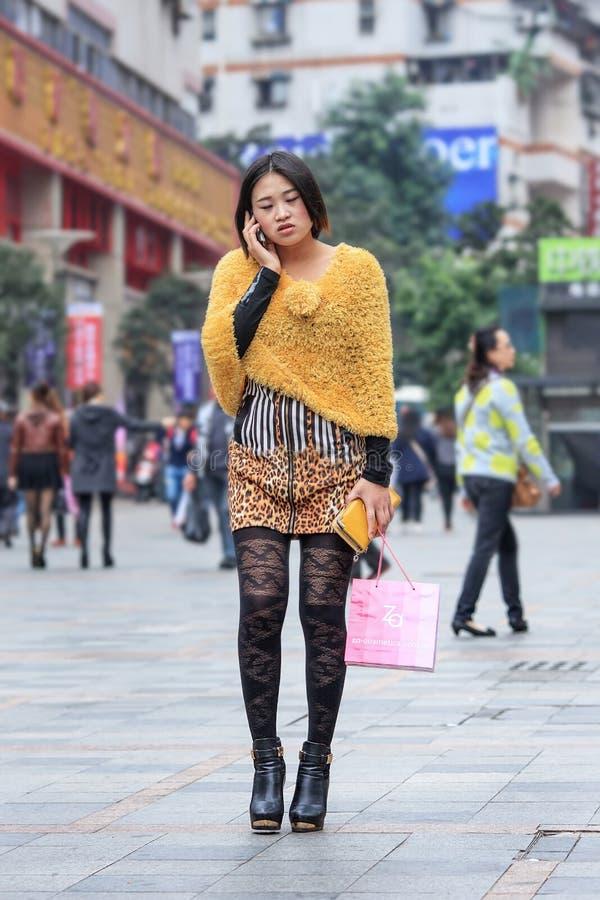 Menina extravagante na área de compra que faz o telefonema, Chong que qing, China foto de stock