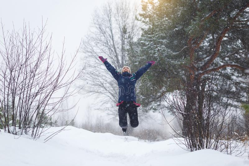 A menina exulta no inverno, uma menina que salta na floresta do inverno fotos de stock royalty free