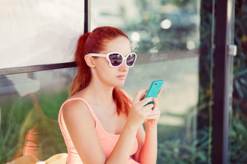 Menina fêmea da mulher que senta-se em uma estação de ônibus usando a aplicação no smartphone para chamar o táxi fotos de stock