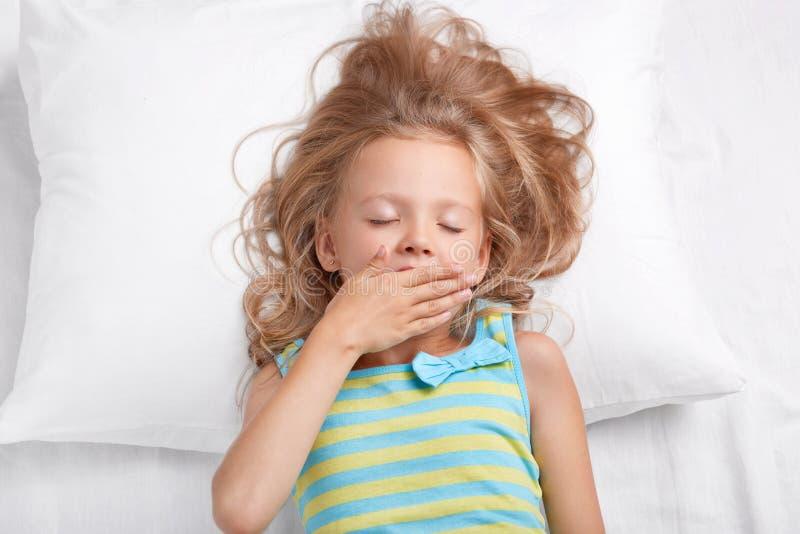 A menina fêmea pequena bonita consideravelmente sonolento mantém os olhos fechados, palma na boca, vestida no nightwear listrado  fotografia de stock
