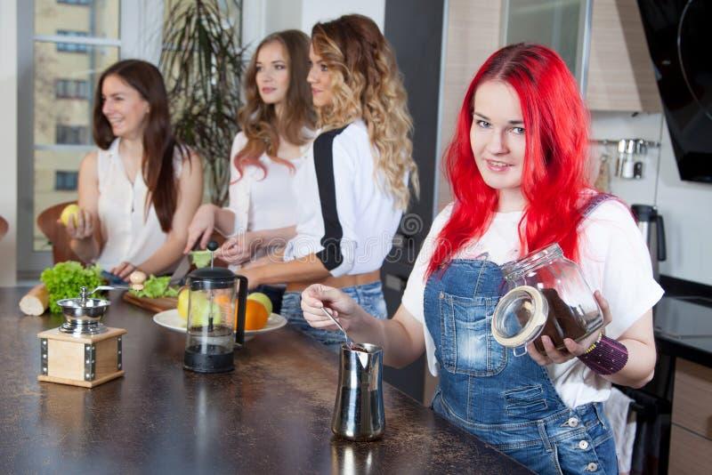 A menina fabrica cerveja o café em uma sala da cozinha, amigos imagem de stock