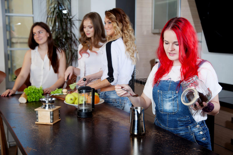 A menina fabrica cerveja o café em uma sala da cozinha, amigos fotografia de stock