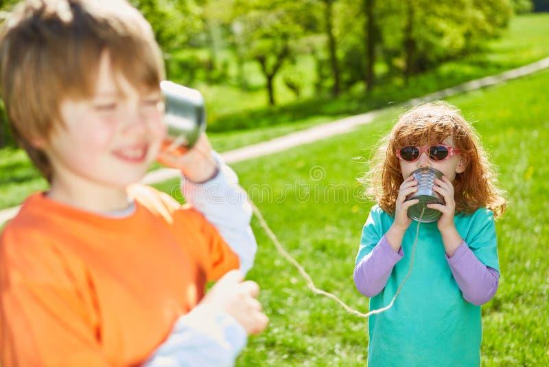 A menina fala em um telefone da lata com o cabo imagem de stock