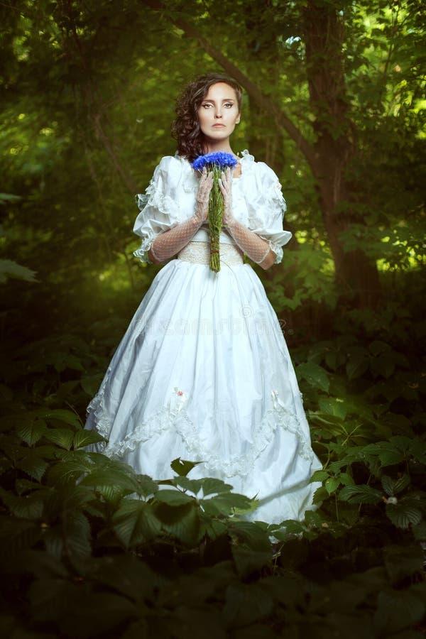 Menina fantástica em um vestido branco com centáureas das flores fotografia de stock royalty free