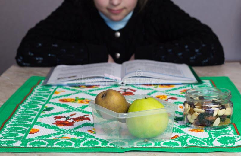 A menina faz as lições, antes que esteja uma maçã e uma pera, uma mistura de frutos secados, maçã imagens de stock royalty free