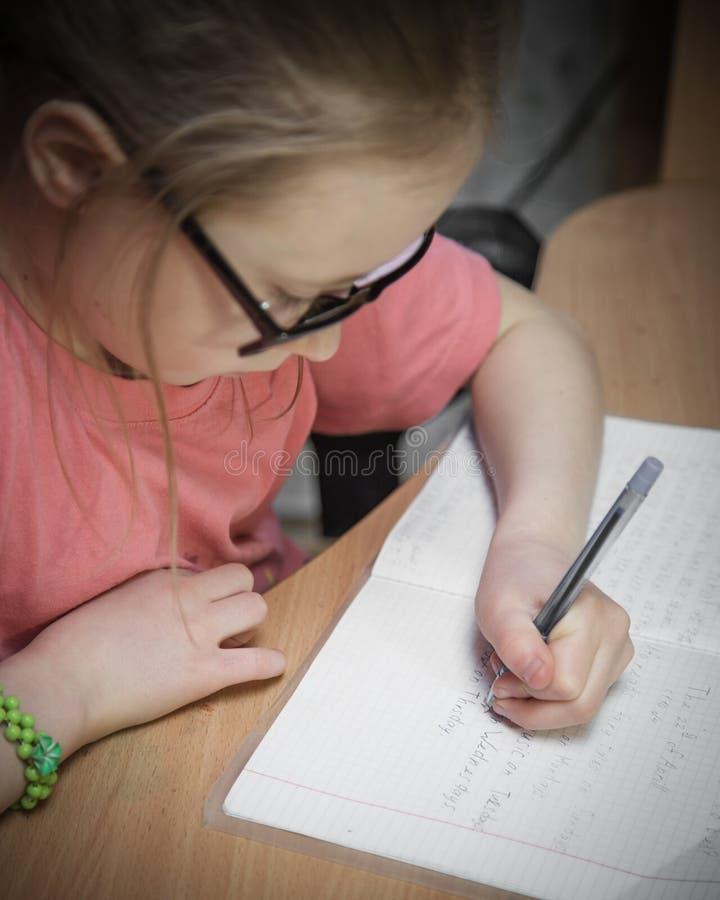 A menina faz lições escritas fotos de stock