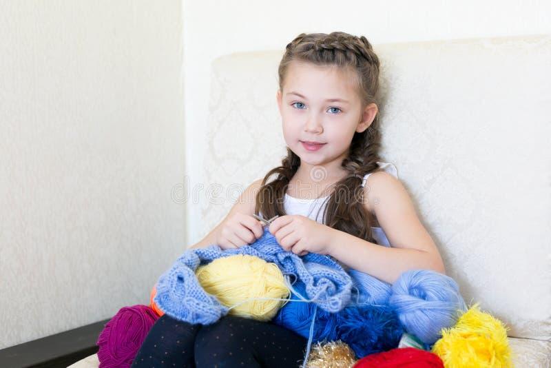 A menina faz malha com confecção de malhas e linha fotografia de stock