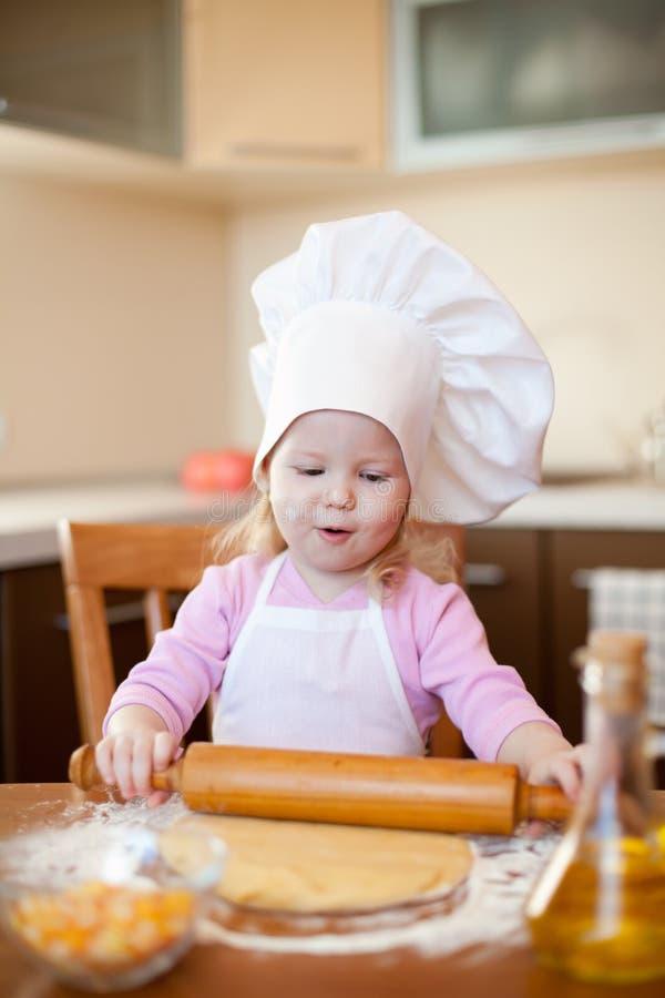 A menina faz a massa de pão na cozinha com pino do rolo imagem de stock royalty free