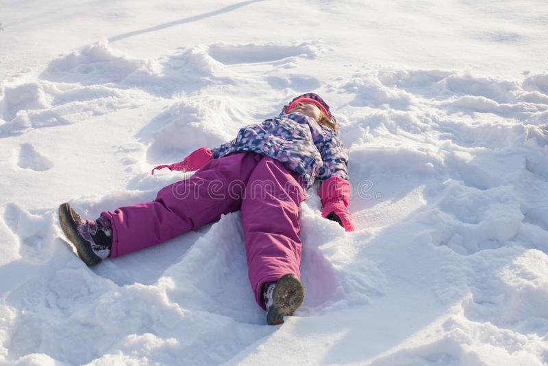 A menina faz o anjo da neve imagens de stock