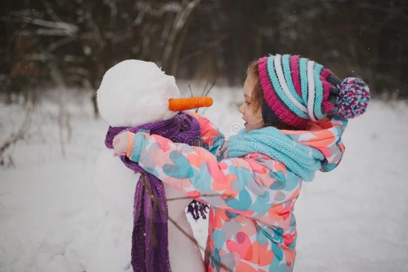 A menina faz o boneco de neve no parque do inverno fotografia de stock royalty free