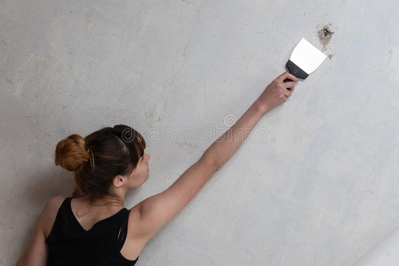 A menina faz o reparo do apartamento Uma mulher conduz uma espátula em um muro de cimento fotografia de stock royalty free