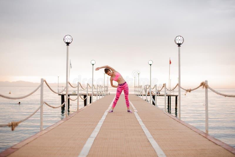 A menina faz os exercícios no nascer do sol perto do mar fotografia de stock royalty free