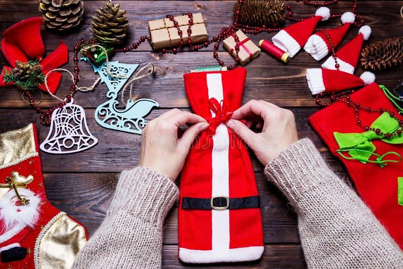 A menina faz presentes do Natal em uma tabela de madeira escura fotografia de stock