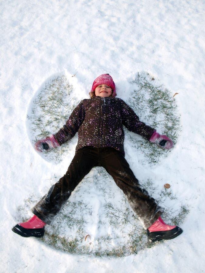 A menina faz um anjo na neve fotografia de stock