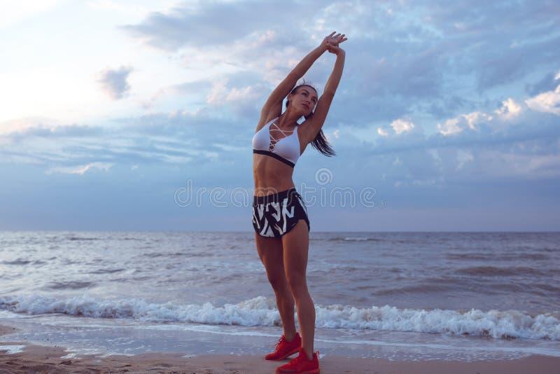 A menina faz um aquecimento antes de fazer esportes cedo na manhã no litoral Uma menina da construção atlética com uma massa seca imagens de stock royalty free