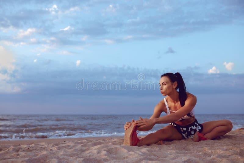 A menina faz um aquecimento antes de fazer esportes cedo na manhã no litoral Uma menina da construção atlética com uma massa seca fotografia de stock royalty free