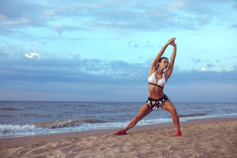 A menina faz um aquecimento antes de fazer esportes cedo na manhã no litoral Uma menina da construção atlética com uma massa seca foto de stock royalty free