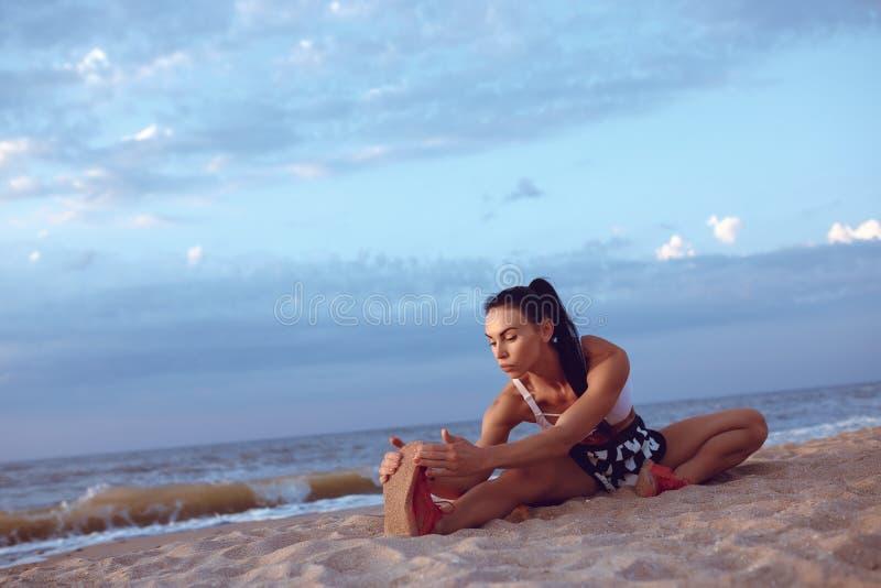 A menina faz um aquecimento antes de fazer esportes cedo na manhã no litoral Uma menina da construção atlética com uma massa seca fotos de stock royalty free