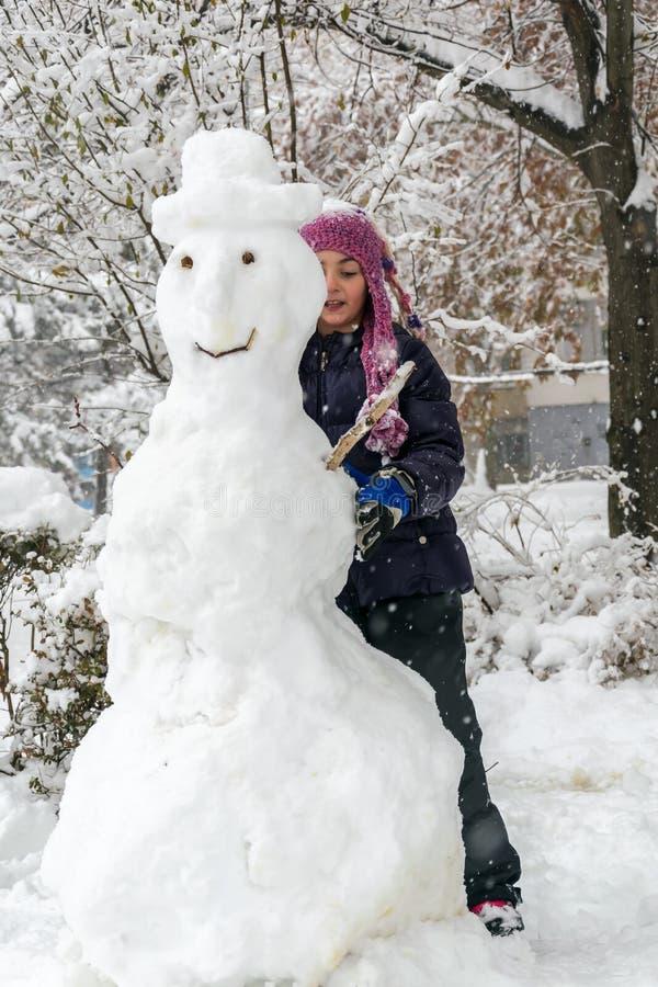 A menina faz um boneco de neve grande fotos de stock royalty free