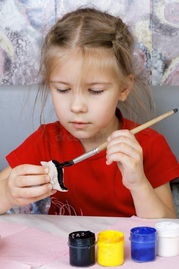 A menina faz um brinquedo da argila fotos de stock