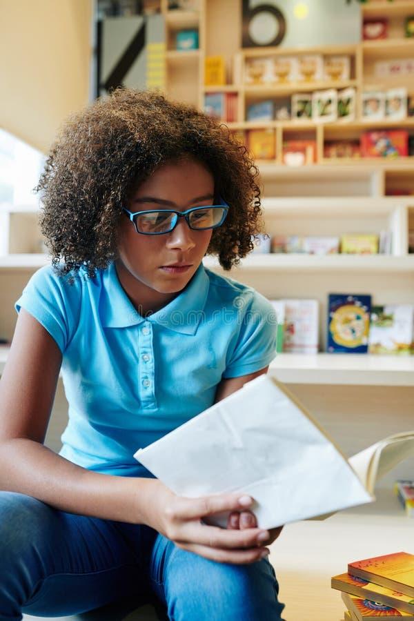 Menina Fazendo Trabalho De Casa Na Biblioteca imagens de stock royalty free