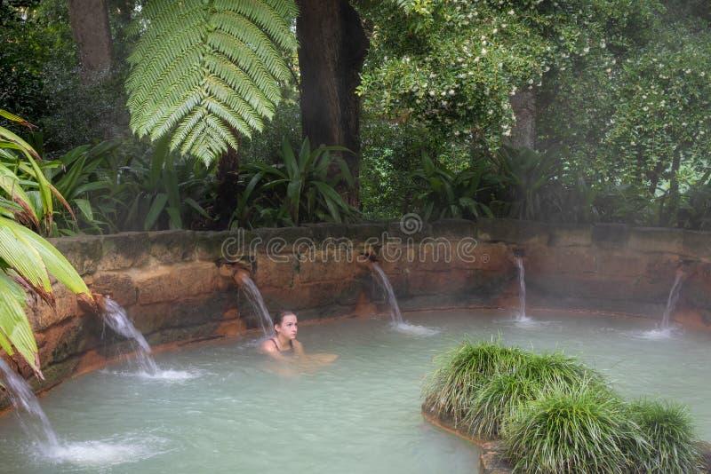 Menina a fazer massagem na piscina mineral térmica jacuzzi no jardim botânico Terra Nostra em Furnas, ilha de São Miguel, Açores imagens de stock royalty free