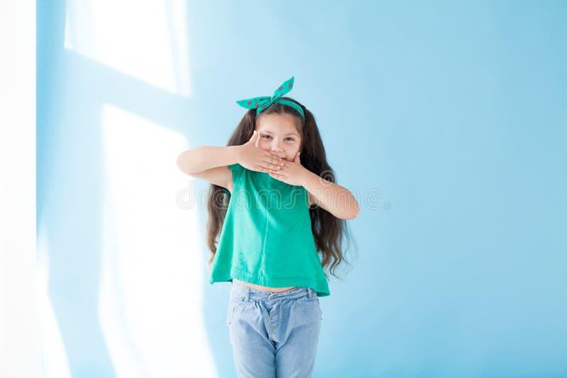 A menina fecha as mãos própria boca agradável imagens de stock