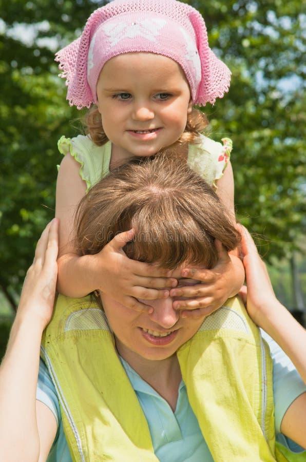 A menina fecha sua mamã dos olhos fotos de stock