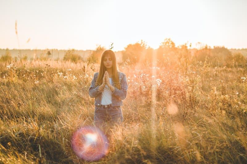 A menina fechado seus olhos, rezando fora, as mãos dobrou-se no conceito da oração para a fé, a espiritualidade e a religião espe imagens de stock