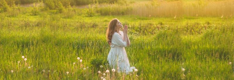 A menina fechou seus olhos, rezando em um campo durante o por do sol bonito M?os dobradas no conceito da ora??o para a f? fotografia de stock