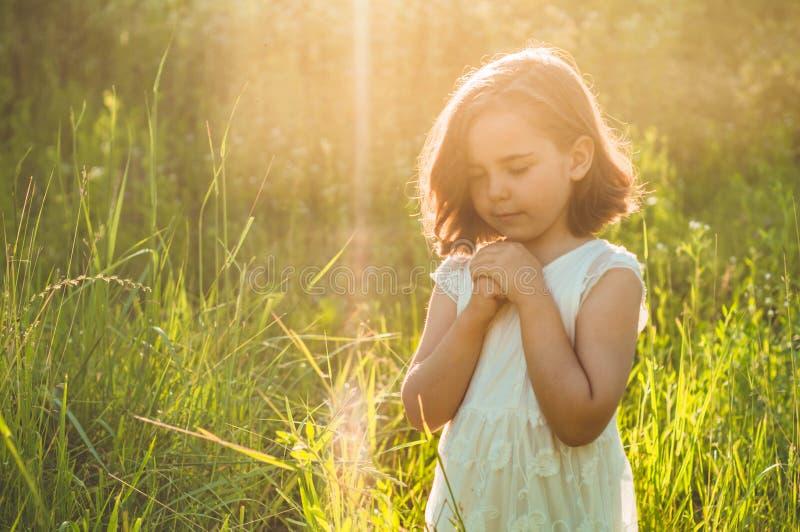 A menina fechou seus olhos, rezando em um campo durante o por do sol bonito M?os dobradas no conceito da ora??o para a f? fotos de stock royalty free