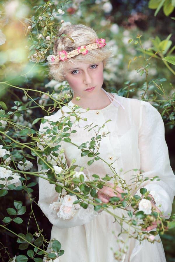Menina feericamente bonita no jardim de rosas imagens de stock royalty free