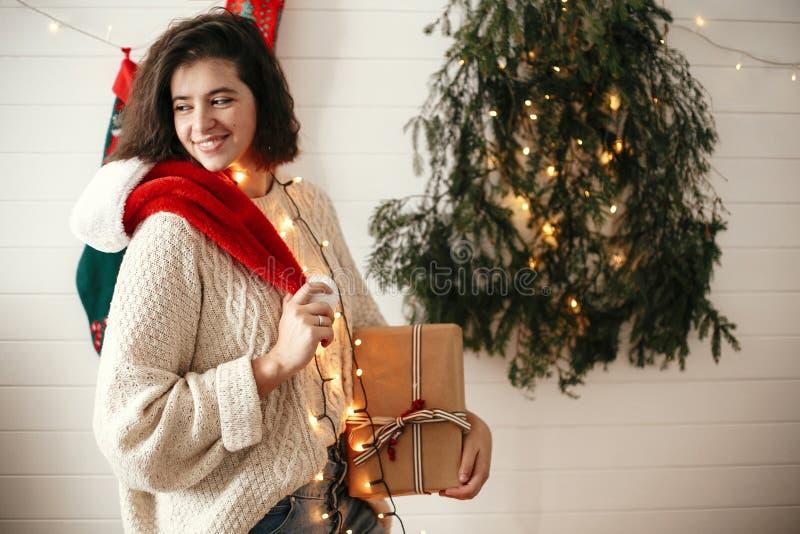 Menina feliz à moda com o chapéu de Santa e a camiseta acolhedor que guardam a caixa de presente do Natal no fundo da árvore de N imagem de stock