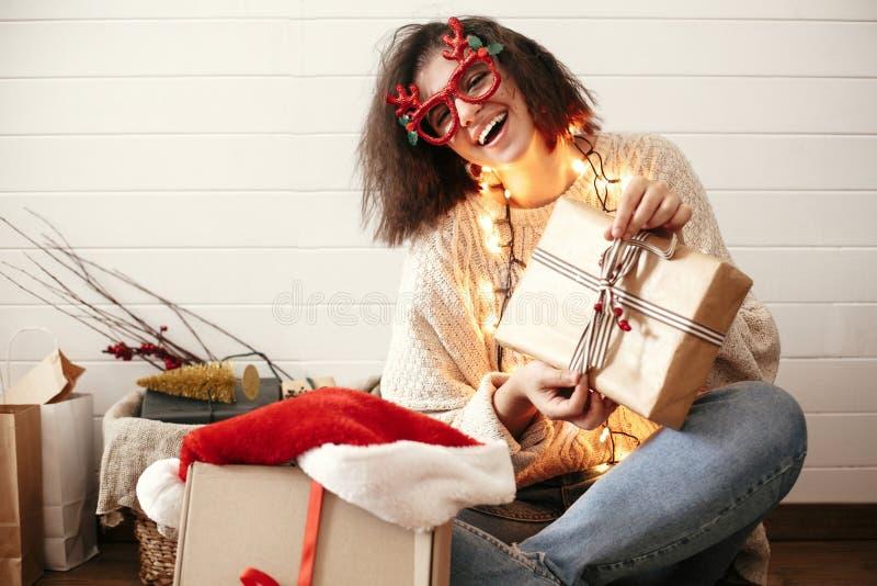 Menina feliz à moda em vidros festivos com os chifres da rena que envolvem presentes do Natal e que sorriem em luzes de Natal nov fotografia de stock royalty free