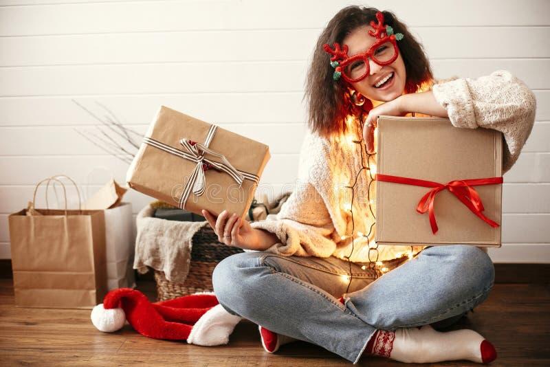 Menina feliz à moda em vidros festivos com os chifres da rena que guardam caixas de presente do Natal em luzes de Natal Mulher no foto de stock royalty free