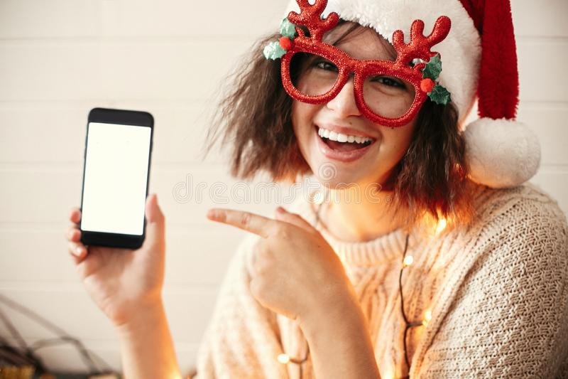 Menina feliz à moda em vidros festivos com os chifres da rena que sorriem e que mostram a telefone a tela vazia em luzes de Natal fotografia de stock