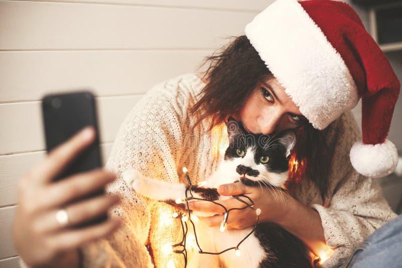 Menina feliz à moda no chapéu de Santa que toma o selfie com o gato bonito em luzes de Natal no fundo dos presentes Mulher nova d fotos de stock