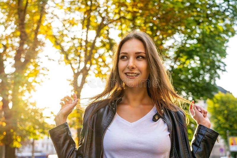 A menina feliz é sorrir exterior com fundo da luz solar foto de stock