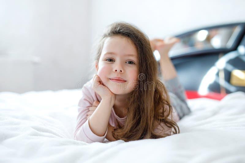 Menina feliz adorável da criança após o sono em sua cama branca no nightwear colorido imagens de stock royalty free