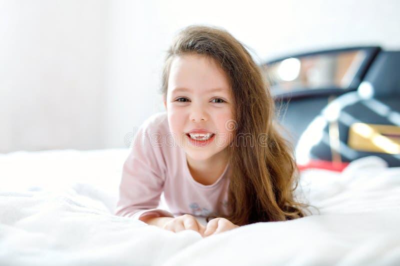 Menina feliz adorável da criança com cabelos longos após o sono em sua cama branca do hotel no nightwear colorido Aluno fotos de stock