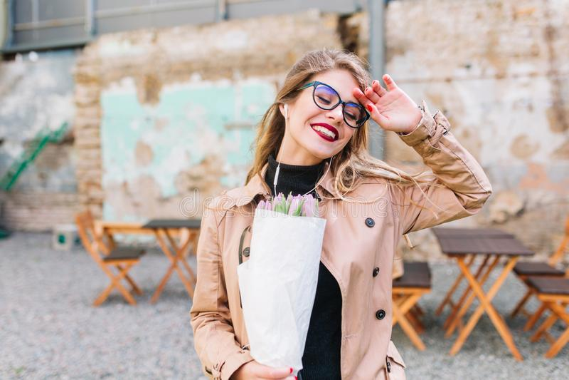 A menina feliz alegre com tulipas roxas veio ao café após um dia ocupado Jovem mulher bonita que comemora seu aniversário dentro fotografia de stock