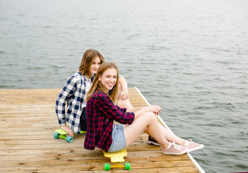 Menina feliz alegre do skater dois no equipamento do moderno que tem o assento em um cais de madeira durante férias de verão fotos de stock