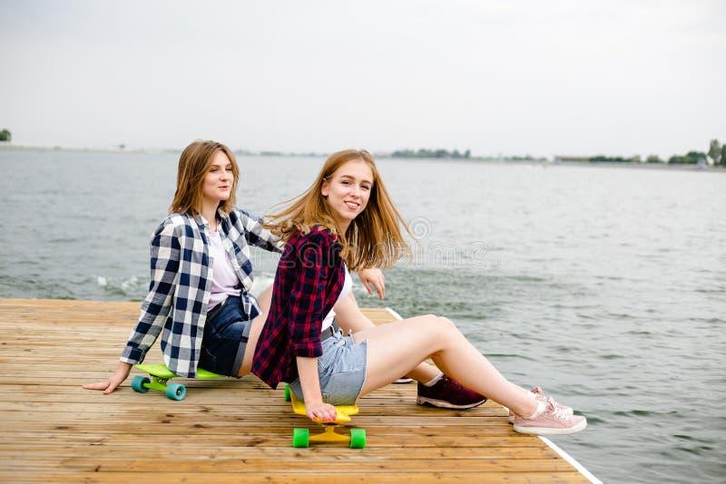 Menina feliz alegre do skater dois no equipamento do moderno que tem o assento em um cais de madeira durante férias de verão imagens de stock