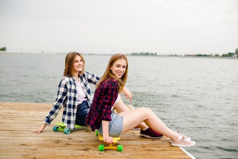 Menina feliz alegre do skater dois no equipamento do moderno que tem o assento em um cais de madeira durante férias de verão foto de stock