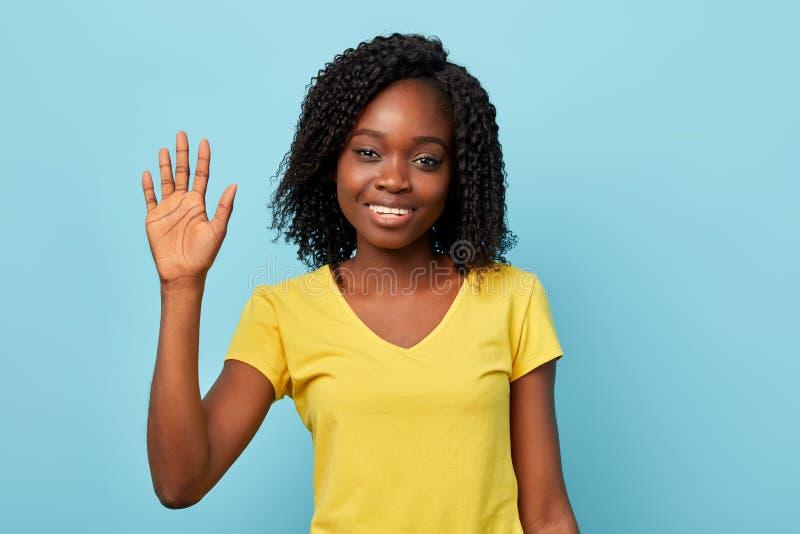 Menina feliz alegre no t-shirt amarelo à moda com braço aumentado que cumprimenta alguém fotos de stock royalty free