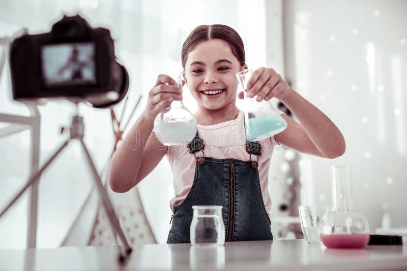 Menina feliz alegre que olha garrafas em suas mãos imagem de stock royalty free