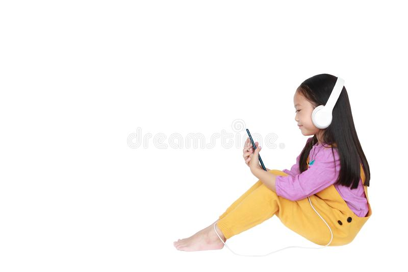 A menina feliz aprecia escutar a m?sica com os fones de ouvido isolados no fundo branco com espa?o da c?pia fotografia de stock