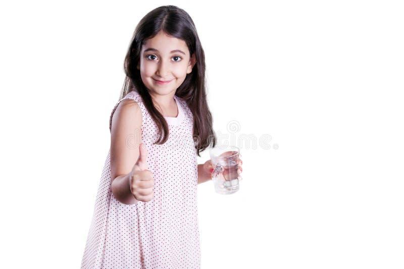 Menina feliz bonita com cabelo escuro longo e o vestido que guardam o vidro da água imagens de stock