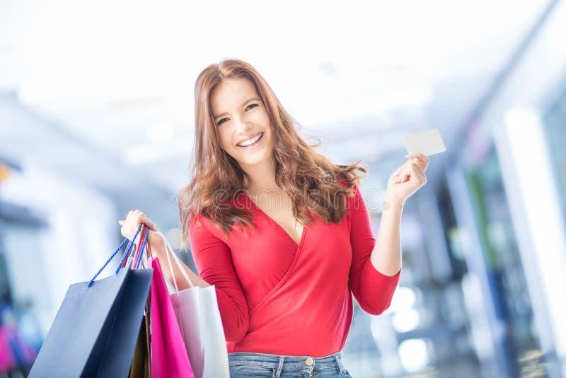 Menina feliz bonita com cartão de crédito e sacos de compras no shopp foto de stock
